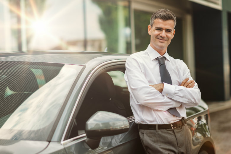 Business man leaning against car