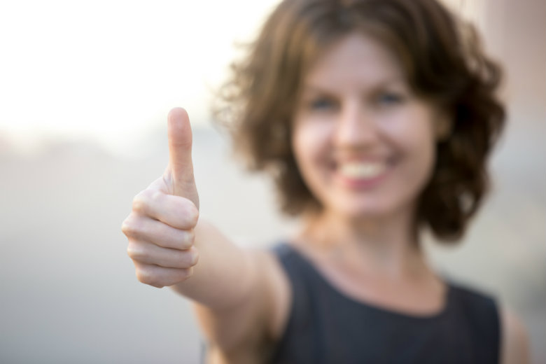 business woman with thumbs up, focus on hand