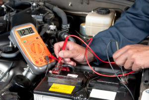 Auto mechanic checking car battert voltage