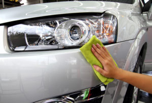 Hand wiping car with polish