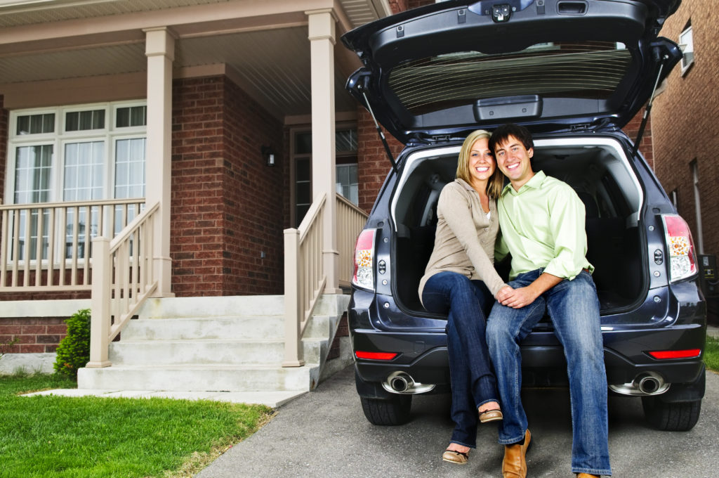 Couple sitting in back of car in driveway