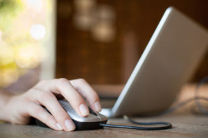 Woman hand with mouse and laptop